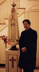 Fr. Khoat next to a statue of Our Lady of Fatima